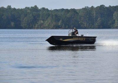 man driving a sheriffs boat side angle
