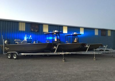 3 custom green law enforcement boats with their blue lights on